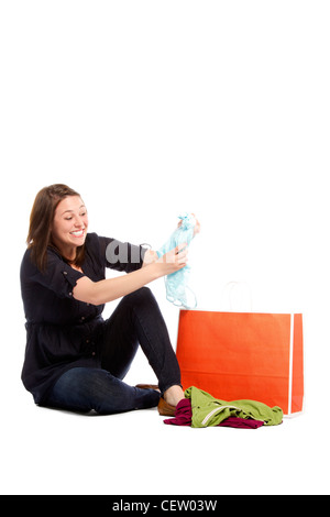 Excited young woman checking new clothes from bag Isolated on white background - Stock Photo