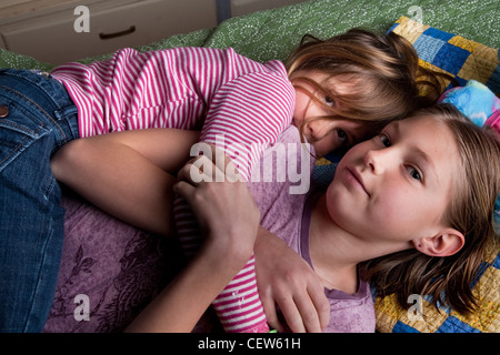 Two sisters snuggling each other on the floor at home. - Stock Photo