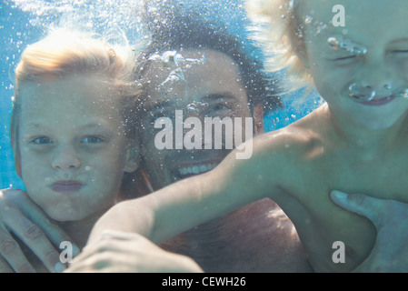 Father and sons swimming underwater - Stock Photo