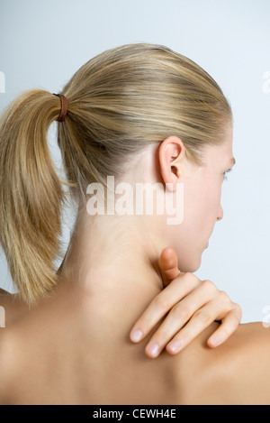 Woman rubbing neck, rear view - Stock Photo