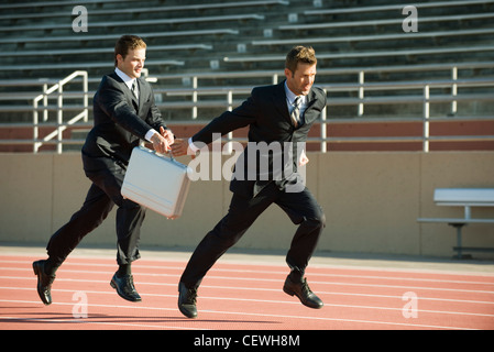 Businessmen running in relay race, handing off briefcase - Stock Photo