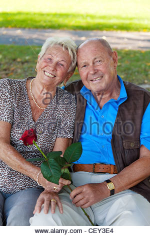 older elderly couple in love. man gives a rose. - Stockfoto