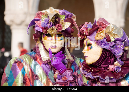 Two people dressed in masquerade masks - Stock Photo