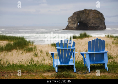 two blue adirondack chairs on a grassy beach with rock formations in the ocean; rockaway beach oregon united states - Stockfoto
