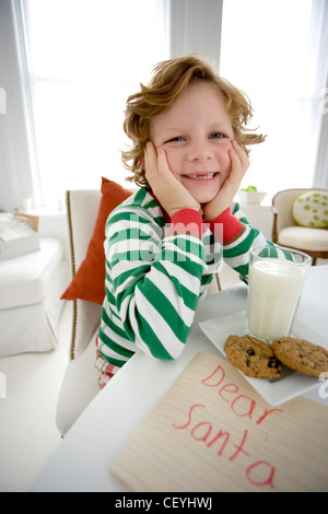 Male child wavy fair hair, wearing a green striped top long sleeves, sitting by the table propping his head on elbows, - Stock Photo