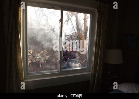 A nine year old boy stares at a broken window. - Stock Photo