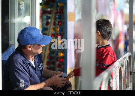 TEMPLE CITY, CA - FEBRUARY 25, 2012 - A young a boy gives a ticket to a man for a ride at the Temple City Fair on - Stock Photo