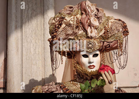 Masked woman with a red rose at the Carnival in Venice, Italy - Stock Photo