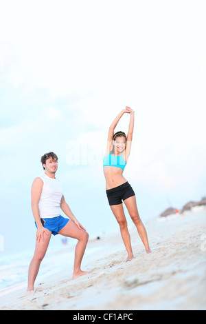 Workout couple exercising and stretching on beach. Young interracial couple, Asian woman, Caucasian man working - Stock Photo