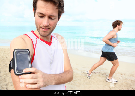 Running workout man with mp3 music player listening to music with mp3 player armband or smart mobile phone. - Stockfoto