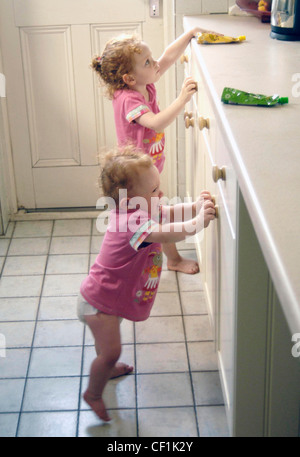Female children with curly red hair, wearing matching pink t shirts, standing in the kitchen - Stock Photo