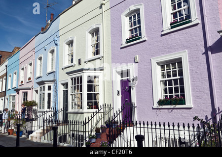 A man and woman talking on the steps outside a pastel coloured terrace house in Bywater Street. - Stock Photo