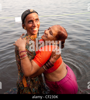 Two women bathing in Ganges River, India - Stock Photo