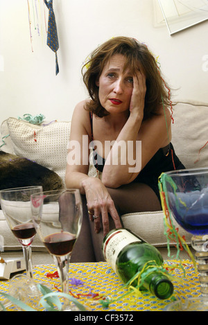 Female brunette hair wearing black dress sitting on edge of sofa leaning forward hand to head looking miserable - Stock Photo
