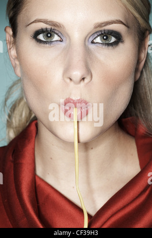 Female with string of spaghetti hanging out of her mouth - Stock Photo