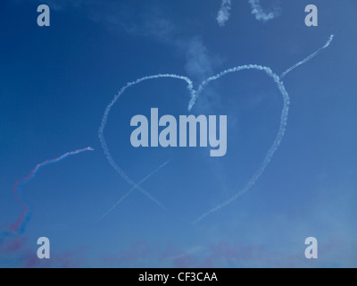 A heart made of smoke hangs in a blue sky over Guernsey after a Red Arrows display. - Stock Photo