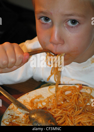 Male child short blond hair wearing white t shirt leaning over table white plate of spaghetti tomato sauce spoon - Stock Photo