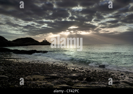 Rays of sunlight bursting through storm clouds over Mumbles Point at dawn. - Stock Photo