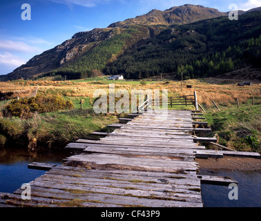 A wooden sheep bridge spans the River Massan in the heart of remote Glen Massan. - Stock Photo
