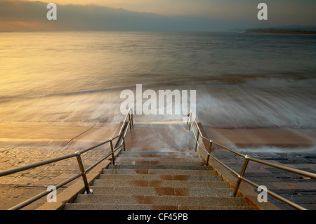 Waves rushing over the beach onto steps at dawn on the seafront at Exmouth. - Stock Photo