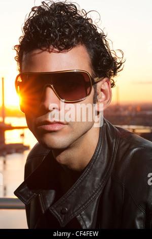 Man in mid twenties wearing glasses during sunset. - Stock Photo