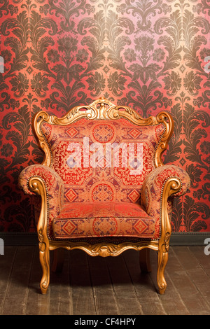 vintage red-yellow chair with gold accents standing beside the wall. wooden floor - Stock Photo