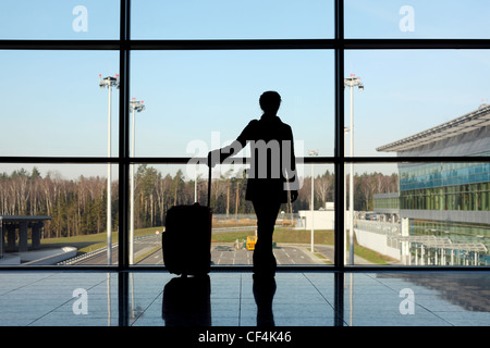 silhouette of girl with luggage standing near window in airport - Stock Photo