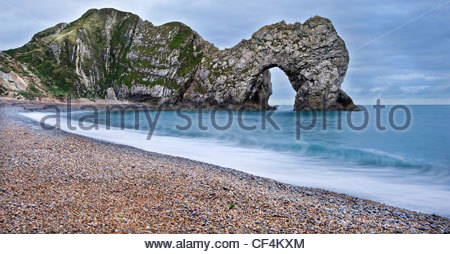 Waves lapping onto the shore by Durdle Door, a natural limestone arch on the Jurassic Coast, at sunrise. - Stock Photo
