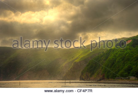 Rays of light breaking through storm clouds over Lynmouth on the North Devon coast at sunrise. - Stock Photo