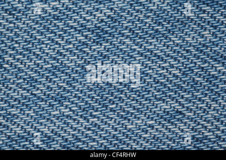 piece of blue denim fabric structure of blue and white threads. close - Stock Photo