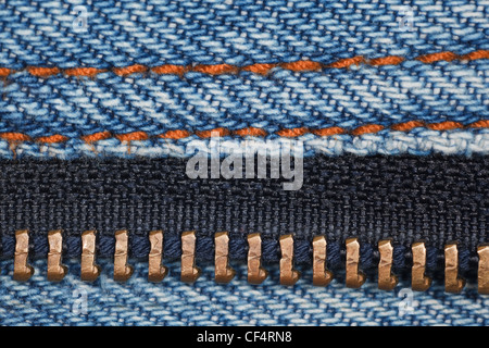 wear a piece of blue denim structure of the yellow line and zipper, macro - Stock Photo