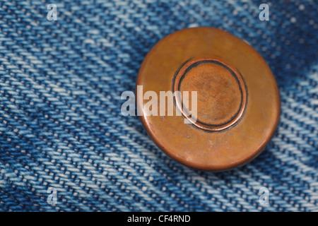 wear a piece of blue denim structure of the yellow button, label was made by me. macro - Stock Photo