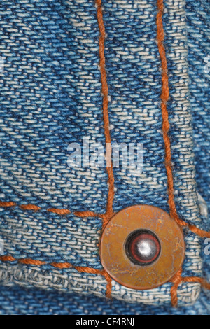 wear a piece of blue denim structure of the yellow lines and rivet - Stock Photo