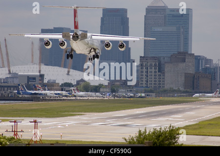 A Swiss Air BAe 146 airplane landing at London City Airport with Docklands and the O2 Arena in the distance. - Stock Photo