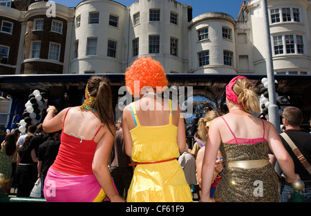 Spectators watch the annual Gay Pride Parade pass through Brighton city centre. - Stock Photo