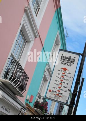 Portobello Market sign on a post in Portobello Road outside brightly painted Victorian terrace properties. - Stock Photo