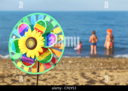 multicolored pinwheel toy with flower on beach, family standing in water - Stock Photo