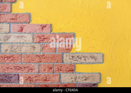 closeup of red brick wall and yellow plaster wall, bright interior - Stock Photo