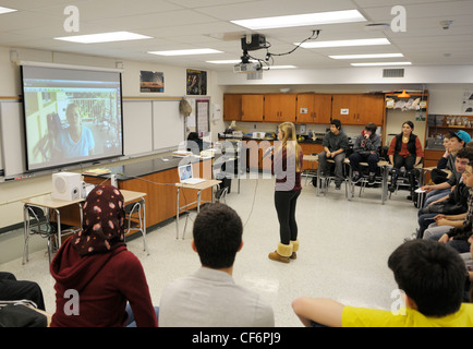 Classroom of American students videoconferencing with a researcher at a field station in Panama- girl with mic asking - Stockfoto