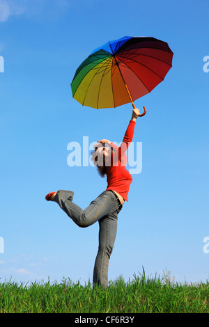 girl standing on one leg on green grass with colorful umbrellas aloft in hand against blue sky - Stock Photo