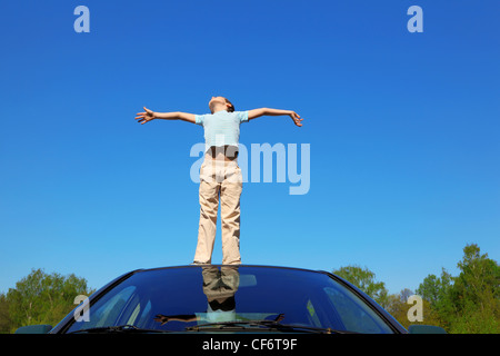 boy standing on roof of car, opening hands, blue sky - Stock Photo