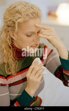 Female long blonde curly hair off face wearing striped poloneck pinching her nose fingertips, holding handkerchief - Stockfoto