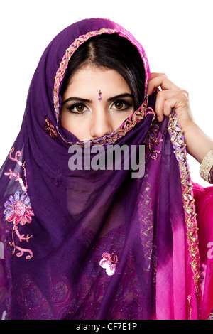 Beautiful Bengali Indian Hindu woman in colorful dress holding veil in front of face, isolated - Stockfoto