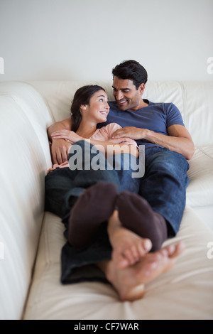 Portrait of a young couple lying on a sofa - Stock Photo