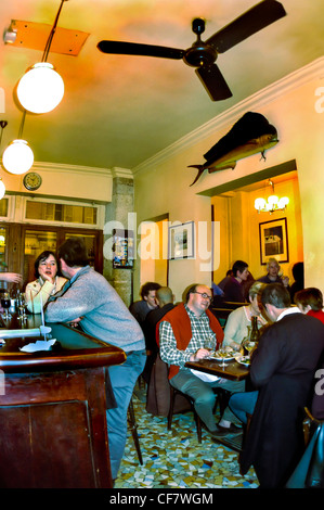 PARIS, France - People Sharing Meals and Drinks inside a local French Bistro, Wine Bar in the Belleville District - Stockfoto
