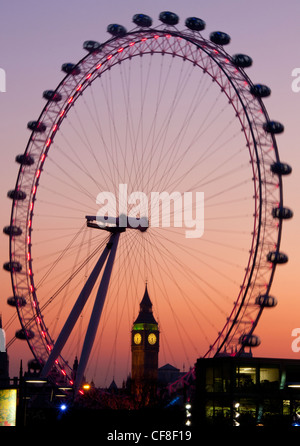Big Ben Clock Tower of Houses of Parliament seen through Millennium Wheel or London Eye at dusk London England UK - Stock Photo