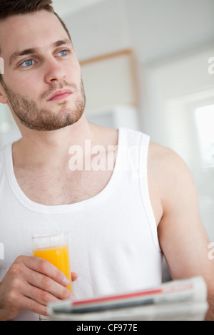 Portrait of a good looking man drinking orange juice while reading the news - Stock Photo