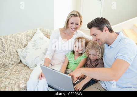 Family on the couch with laptop - Stock Photo