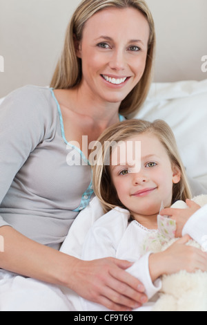 Mother holding her daughter on the bed - Stock Photo