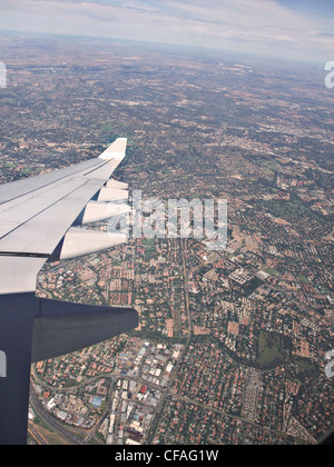 Airplane wing over Johannesburg - Stock Photo